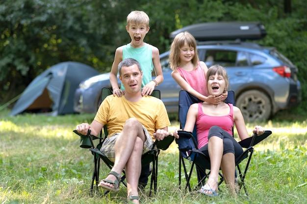 Pais de família jovens felizes e seus filhos descansando juntos no local de acampamento no verão.