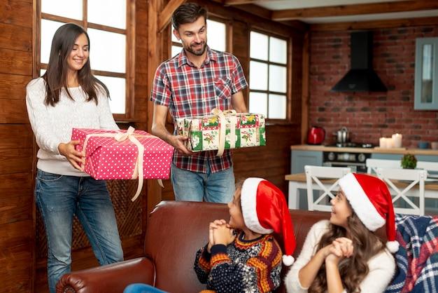 Pais de tiro médio surpreendendo crianças com presentes