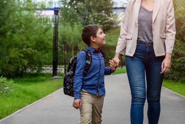 Pais e alunos da escola primária andam de mãos dadas