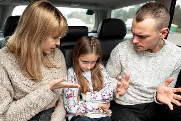 Pais e criança discutindo no carro