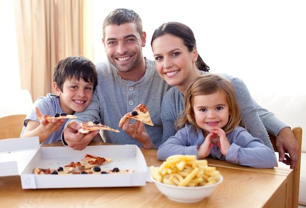 Pais e crianças comendo pizza e batatas fritas em casa