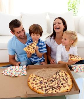 Pais e crianças comendo pizza na sala de estar