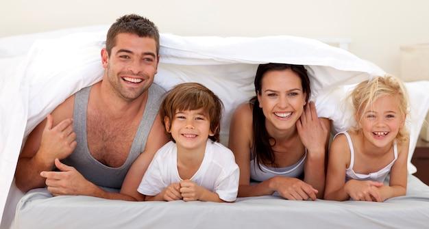 Pais e crianças que brincam na cama dos pais