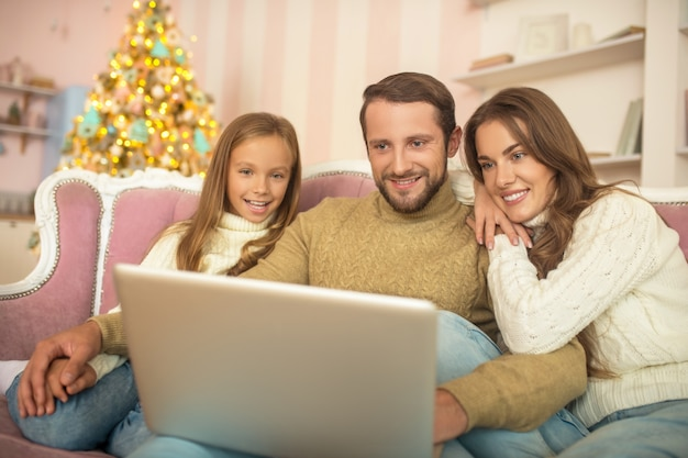 Pais e filha assistindo a algo em um laptop