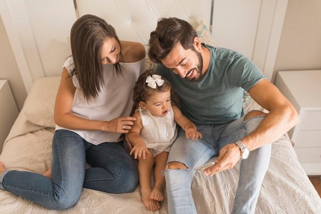 Pais e filha assistindo vídeo no smartphone