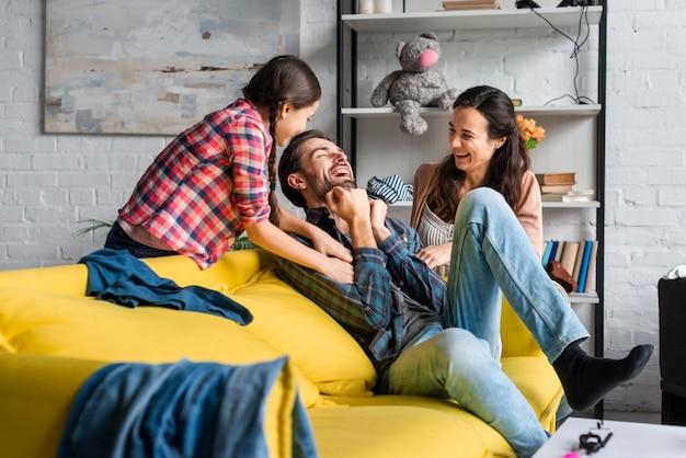 Pais e filha brincando na sala de estar
