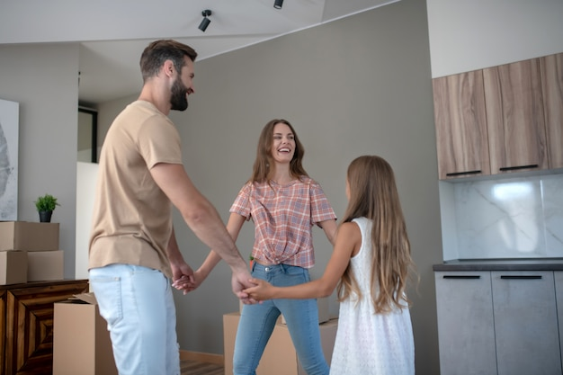 Pais e filha dançando e de mãos dadas