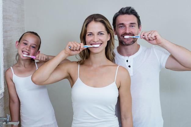 Pais e filha escovando os dentes no banheiro