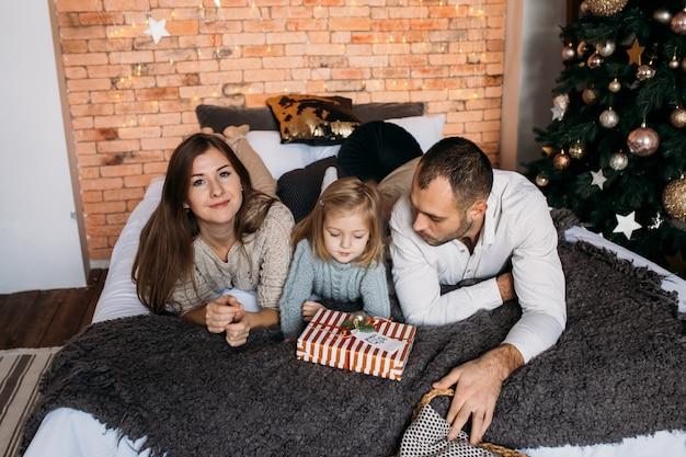 Pais e filha na cama em casa