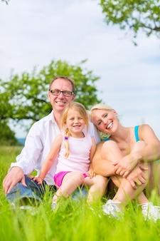 Pais e filha sentados na grama ou no campo