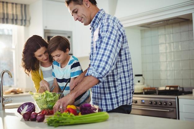 Pais e filho a preparar salada na cozinha