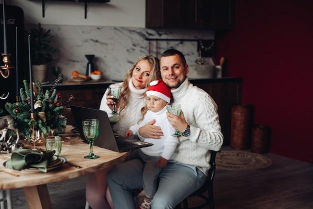 Pais e filho fofo com chapéu de papai noel segurando óculos enquanto jantam de natal e usando laptop