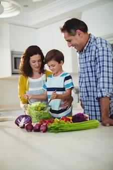 Pais e filho misturando a salada na cozinha