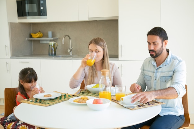 Pais e filho tomando café da manhã, bebendo suco de laranja, sentados à mesa de jantar com frutas e biscoitos.