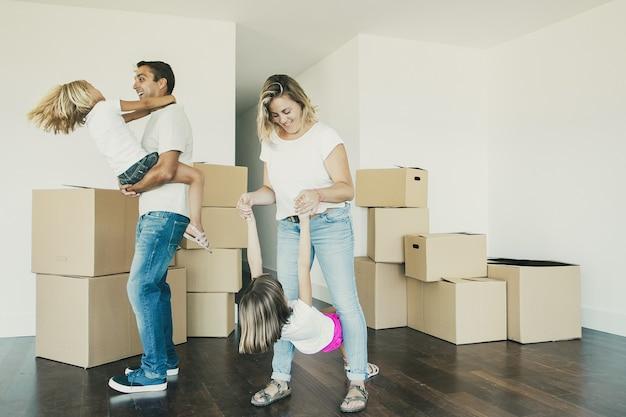 Pais e filhos alegres curtindo a nova casa, dançando e se divertindo perto de pilhas de caixas no quarto vazio