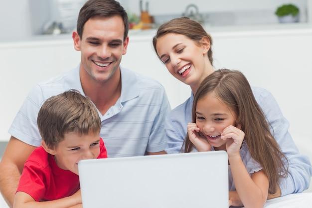 Pais e filhos alegres usando um laptop