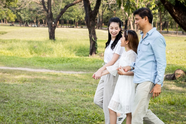 Pais e filhos andando de mãos dadas no parque.