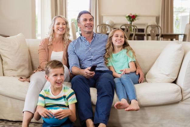 Pais e filhos assistindo tv na sala de estar