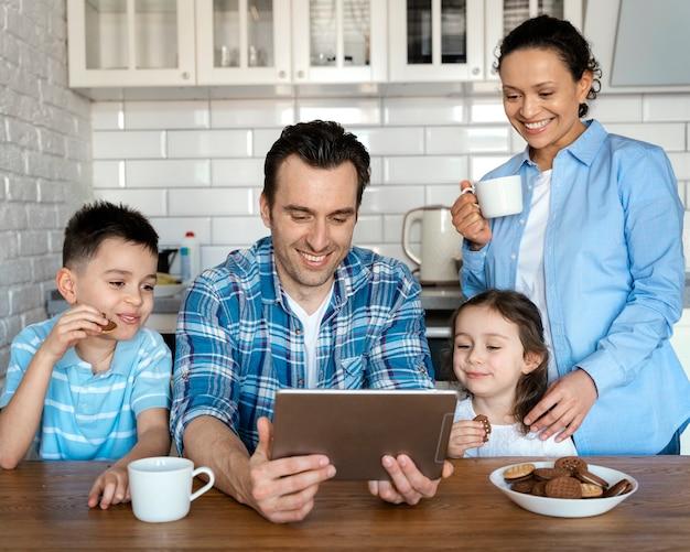 Pais e filhos com tiro médio com tablet