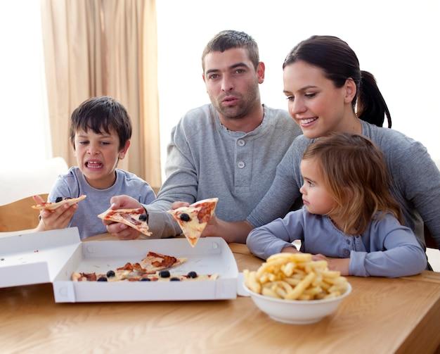 Pais e filhos comendo pizza e batatas fritas em um sofá