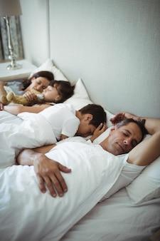 Pais e filhos dormindo na cama