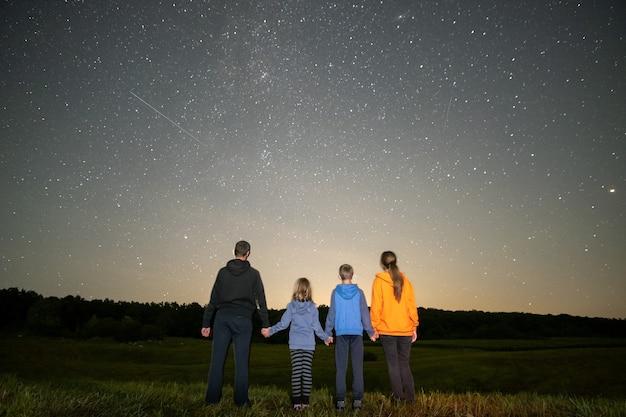 Pais e filhos em pé no campo noturno, observando o céu escuro com muitas estrelas brilhantes.
