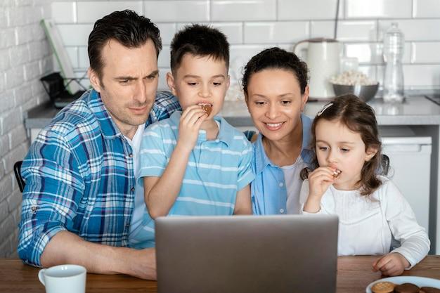 Pais e filhos em planos médios com laptop
