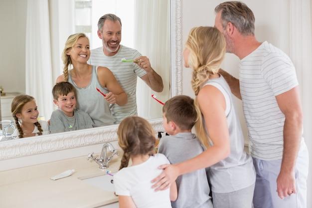 Pais e filhos escovando os dentes no banheiro