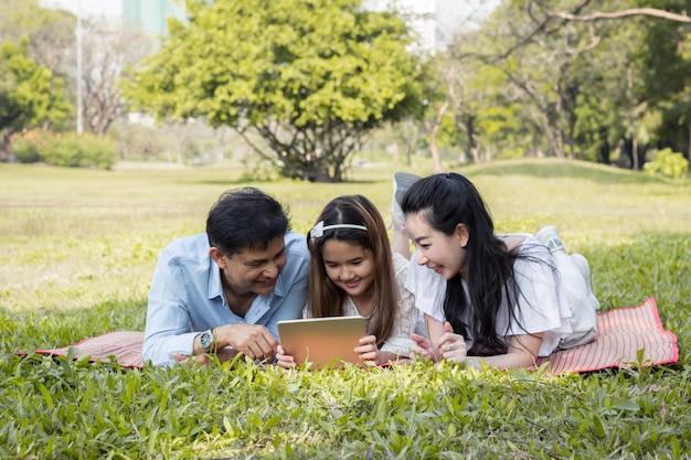 Pais e filhos estão jogando o tablet no tapete.