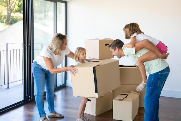 Pais e filhos felizes comemorando a compra de um apartamento, abrindo caixas e se divertindo em seu novo apartamento