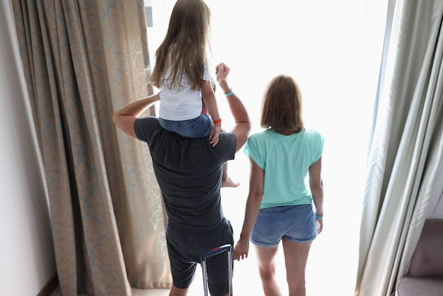 Pais e filhos ficam em quartos de hotel olhando pela janela