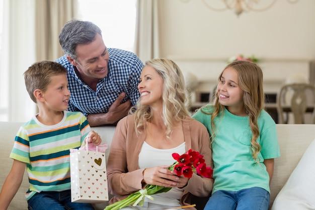 Pais e filhos interagindo no sofá com presente na sala de estar