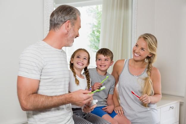 Pais e filhos interagindo uns com os outros enquanto escovam os dentes no banheiro