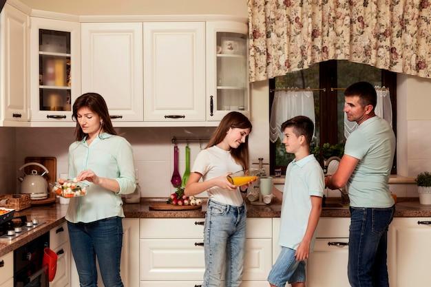 Pais e filhos juntos a preparar comida na cozinha
