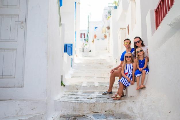 Pais e filhos na rua da aldeia tradicional grega típica na ilha de mykonos, na grécia