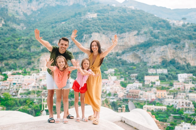 Pais e filhos posando na cidade de positano, na itália, na costa de amalfi