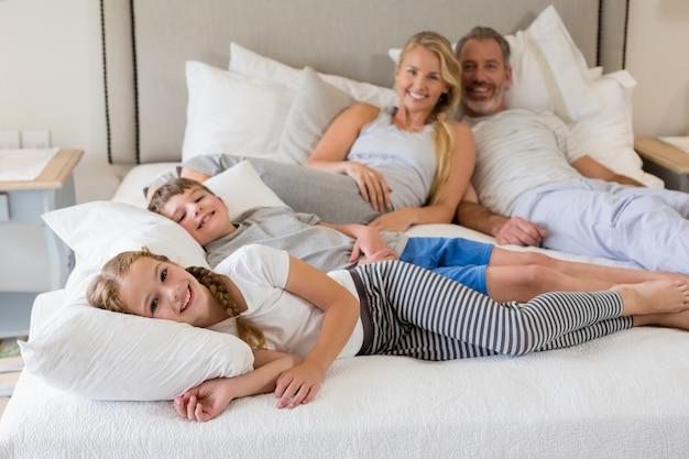 Pais e filhos relaxantes na cama no quarto