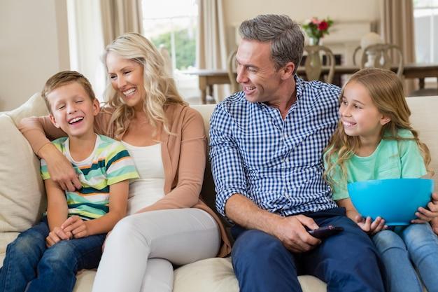 Pais e filhos se divertindo enquanto assistia tv na sala de estar