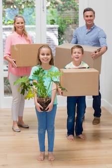 Pais e filhos segurando caixas de papelão na sala de estar em casa