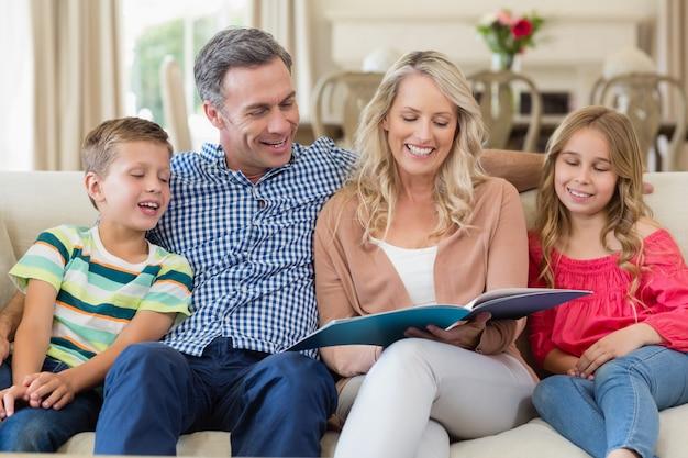Pais e filhos sentados juntos no sofá com o álbum de fotos
