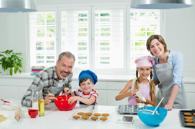 Pais e filhos sorrindo e preparando biscoitos na cozinha