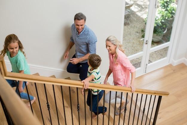 Pais e filhos subindo as escadas em casa