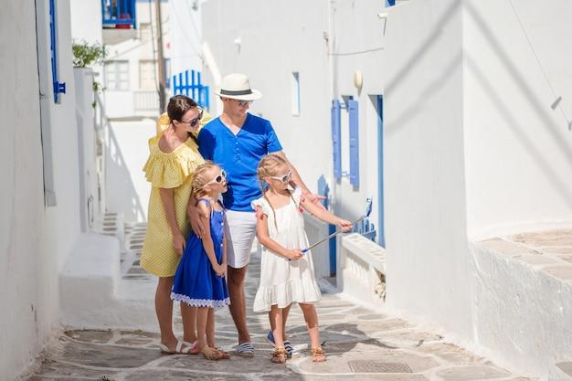 Pais e filhos, tendo selfie foto fundo míconos, cidade na grécia