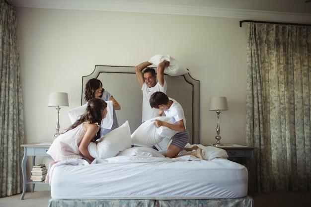 Pais e filhos tendo travesseiro lutar na cama