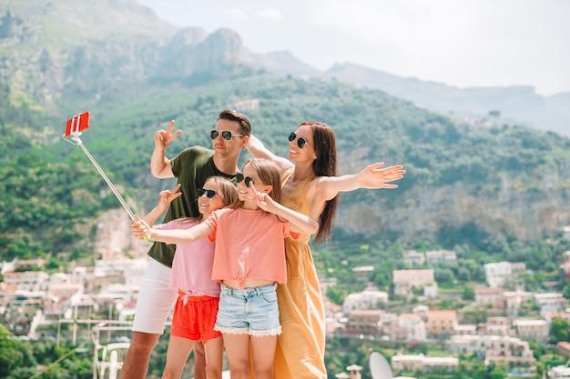 Pais e filhos tirando foto de selfie na cidade de positano, na itália, na costa de amalfi
