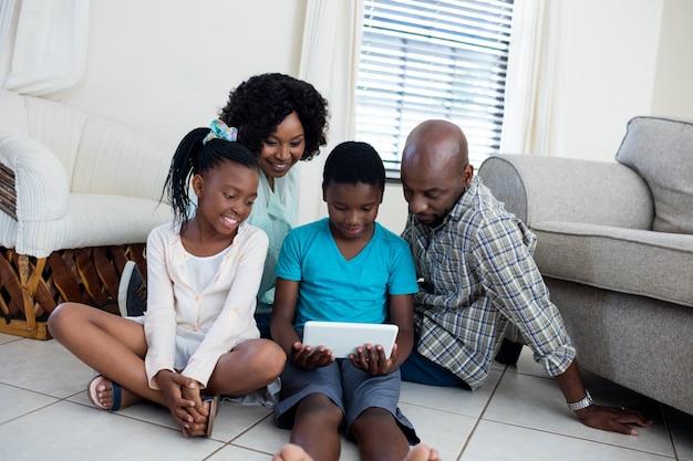 Pais e filhos usando tablet digital na sala de estar