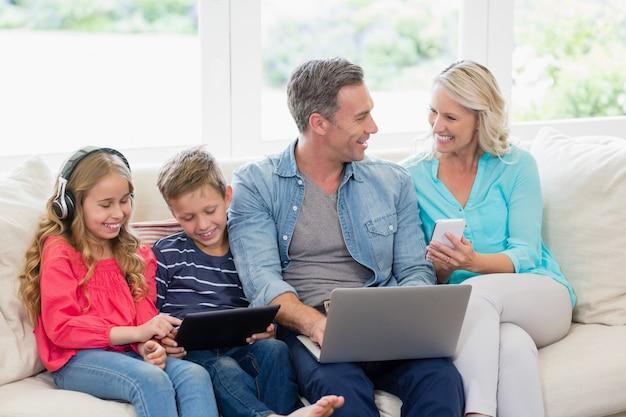 Pais e filhos usando tablet digital, telefones celulares e laptop