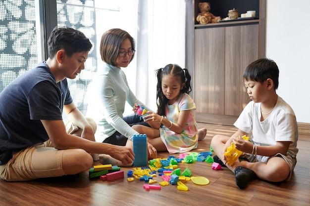 Pais e filhos vietnamitas sentados no chão da sala de estar brincando com brinquedos e blocos de plástico
