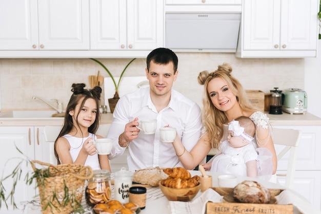 Pais e seus dois filhos comendo e bebendo chá na mesa da cozinha