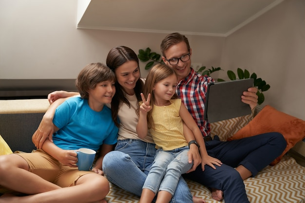 Pais e seus dois filhos pequenos sentados no sofá da sala de estar e usando um tablet digital, eles